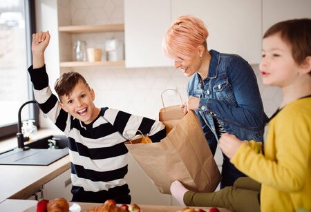 A young woman with two children unpacking shopping in a kitchen.