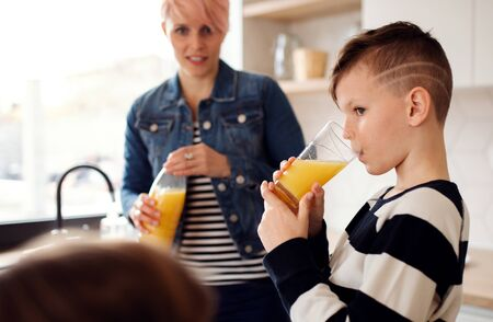 A young woman with children drinking juice in a kitchen.