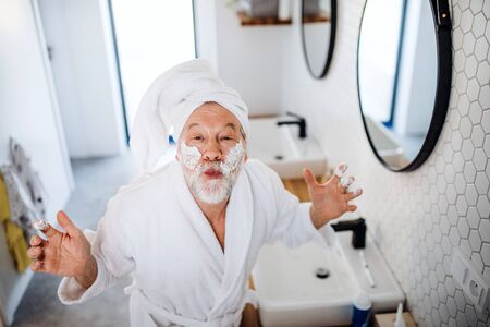 A senior man doing morning routine in bathroom indoors at home. Фото со стока
