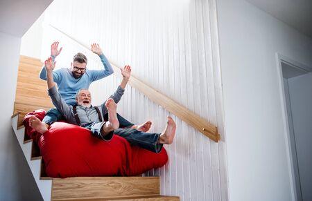 Un fils hipster adulte et un père senior à l'intérieur à la maison, s'amusant.