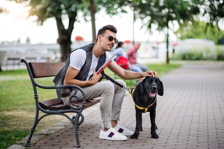 Young blind man with white cane and guide dog sitting in park in city. Stok Fotoğraf