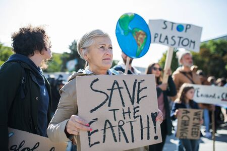 Senior with placard and poster on global strike for climate change. Reklamní fotografie