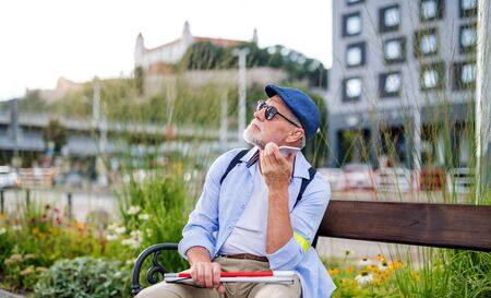 Senior blind man with smartphone sitting on bench in park in city.