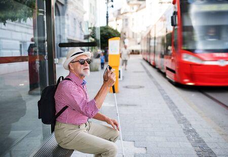 Homme aveugle senior avec canne blanche en attente de transports publics en ville.