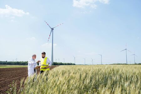 Engineers standing on wind farm, making notes.