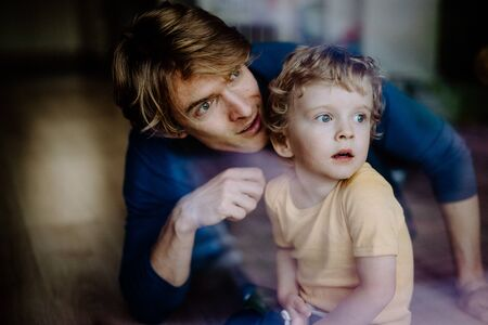 A happy father with a toddler son at home. Shot through glass.