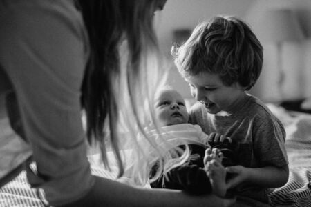 A beautiful young mother with a newborn baby and his brother at home.