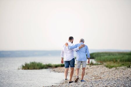 Rear view of senior father and mature son walking by the lake. Copy space.