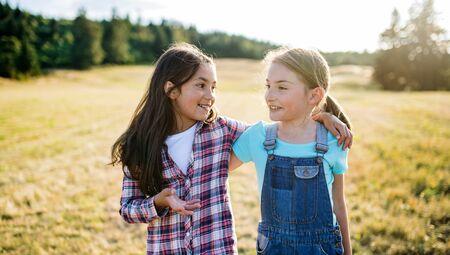 Two school children walking on field trip in nature, talking. Zdjęcie Seryjne