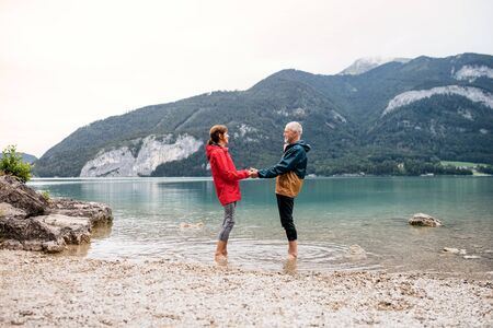 A senior pensioner couple hikers standing barefoot in lake in nature.