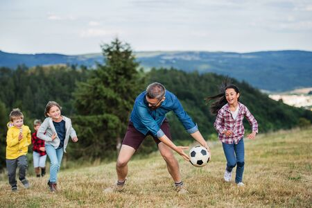 Group of school children with teacher on field trip in nature, playing with a ball.