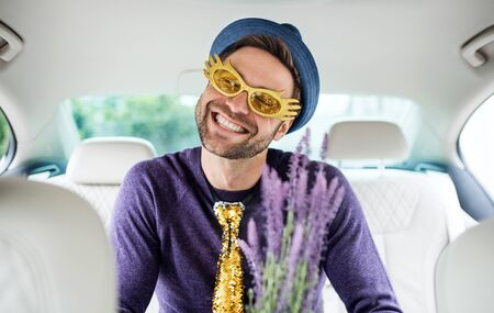 Cheerful man with party accessories sitting in car, having fun.