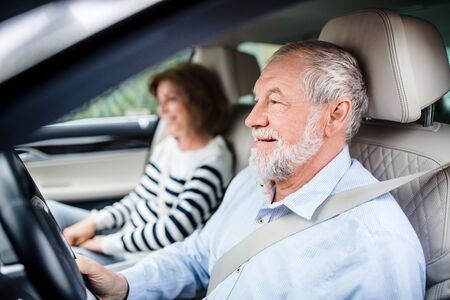 Felice coppia senior con smartphone seduto in macchina, guida,. Archivio Fotografico