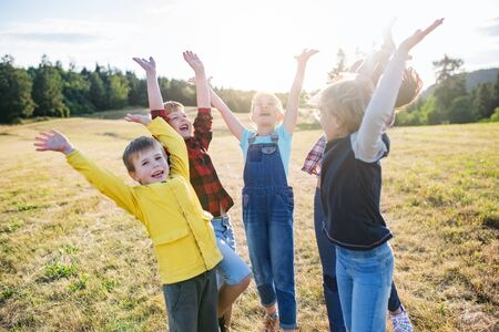 Group of school children standing on field trip in nature, playing. Zdjęcie Seryjne