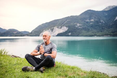 A senior man pensioner sitting by lake in nature, doing yoga exercise. Stock Photo