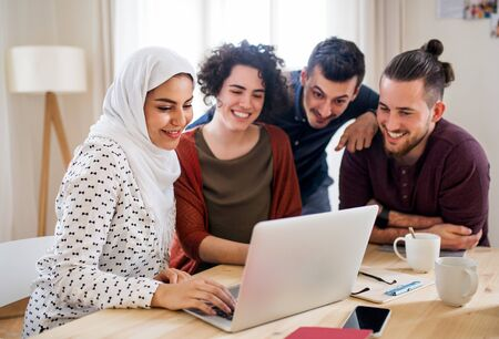 A multi-ethnic group of young friends with laptop indoors, house sharing concept.