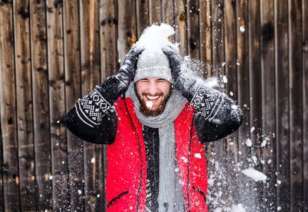 Young man standing against wooden background outdoors in winter, having fun. Фото со стока