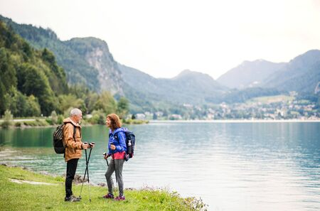 A senior pensioner couple hikers standing by lake in nature, talking.
