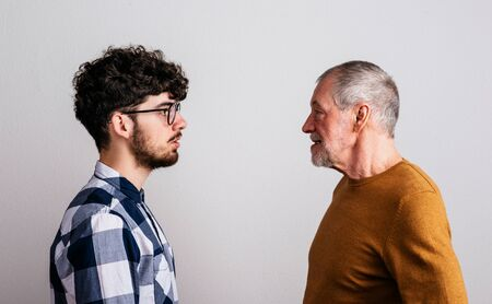 Portrait of a serious senior father and young son in a studio. Banco de Imagens
