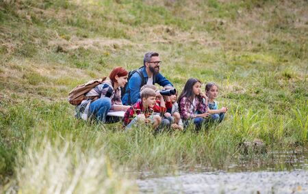 Group of school children with teacher on field trip in nature. 免版税图像