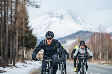 Group of mountain bikers riding on road outdoors in winter.
