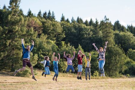Group of school children with teacher on field trip in nature, jumping.