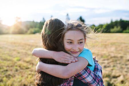 Two school children walking on field trip in nature, hugging.