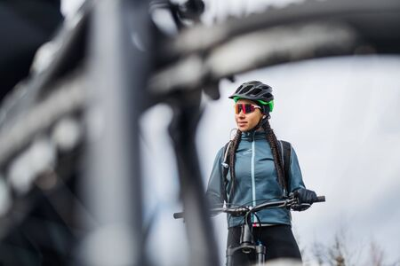Female mountain biker standing on road outdoors in winter.