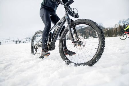 Midsection of mountain biker riding in snow outdoors in winter. Stok Fotoğraf