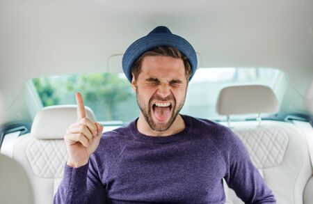 Cheerful man with hat sitting in car, having fun.