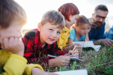 Gruppe von Schulkindern mit Lehrer auf Exkursion in die Natur.
