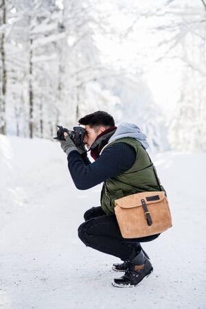 Young man with camera standing outdoors in snow in winter forest, taking photos.