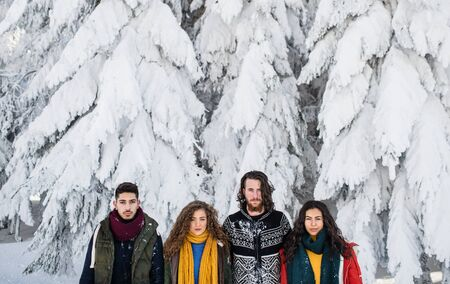 A group of young friends on a walk outdoors in snow in winter.