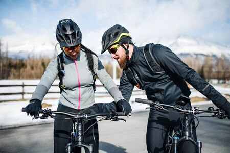 Two mountain bikers riding on road outdoors in winter.