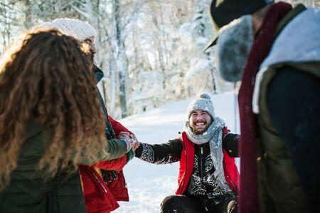 Groupe de jeunes amis en promenade à l'extérieur dans la neige dans la forêt d'hiver, s'amusant.