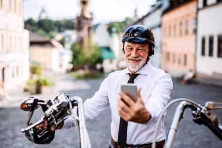 A senior businessman with motorbike in town, using smartphone. Stok Fotoğraf
