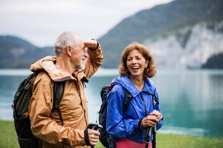 Ein älteres Rentnerehepaar, das am See in der Natur wandert und spricht.