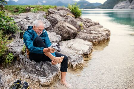 A senior man hiker sitting by lake in nature, taking shoes off. Copy space. Stockfoto