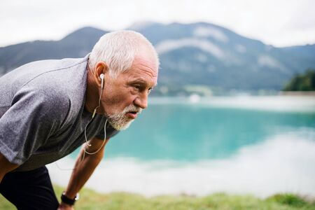A senior man with earphones standing by lake in nature, doing exercise.