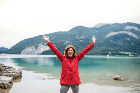 A front view of senior woman hiker standing by lake in nature, stretching arms. 版權商用圖片