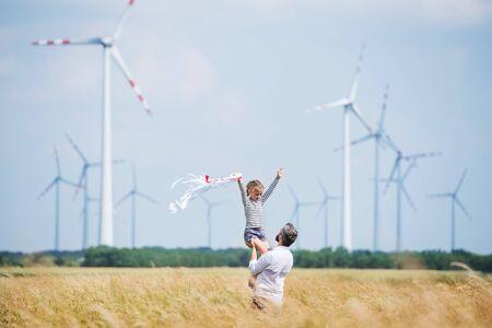Padre maduro con hija pequeña de pie en el campo en el parque eólico.