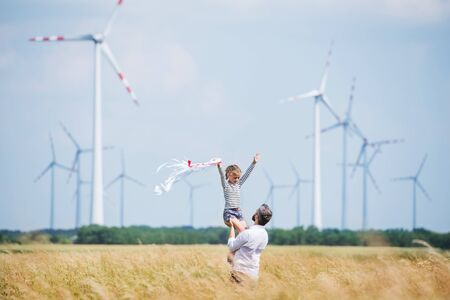 Volwassen vader met kleine dochter staande op veld op windmolenpark.