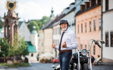 A senior businessman with motorbike and helmet in town, standing.