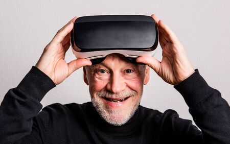 Portrait of a cheerful senior man with VR goggles in a studio.