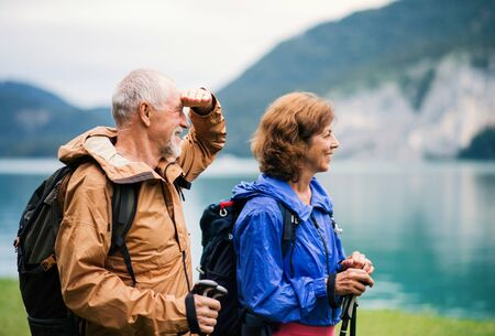 Senior pensioner couple hiking by lake in nature, holding hands.