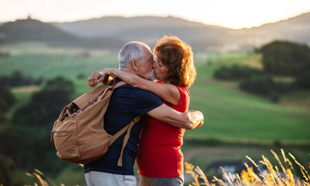 Senior tourist couple travellers with backpacks hiking in nature, kissing. Reklamní fotografie - 133284939