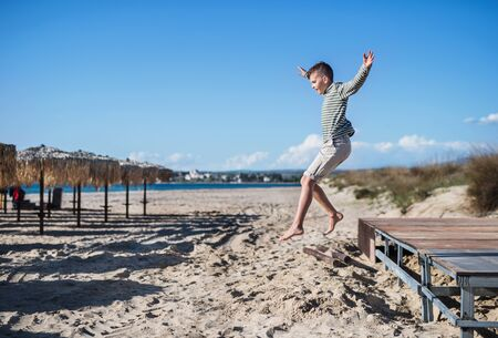 A small boy playing outdoors on sand beach, jumping.