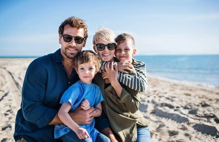 Young family with two small children sitting outdoors on beach. Reklamní fotografie