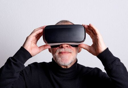 Portrait of a senior man with VR goggles in a studio. Stok Fotoğraf