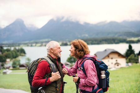 Senior pensioner couple with nordic walking poles hiking in nature, talking. Reklamní fotografie